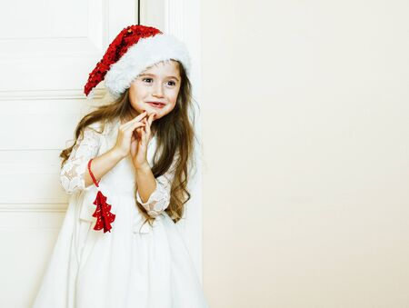 little cute girl in santas red hat waiting for Christmas gifts. Standard-Bild - 130144354