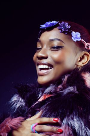 young pretty african american woman in spotted fur coat and flow