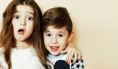 little cute boy and girl hugging playing on white background