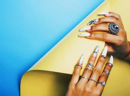 woman hands holding colorful paper copyspace wearing a lot of jewelry Фото со стока