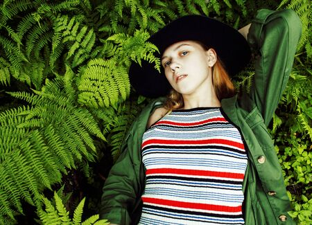 Pretty young blond girl hipster in hat among fern