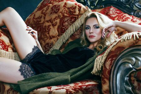 young blond woman in luxury interior laying on an antique chair