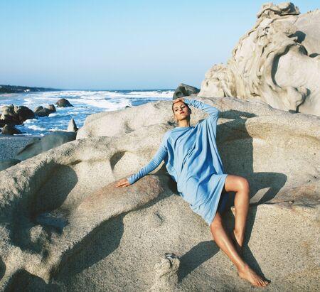beauty young woman among rocks at sea dreaming relaxing
