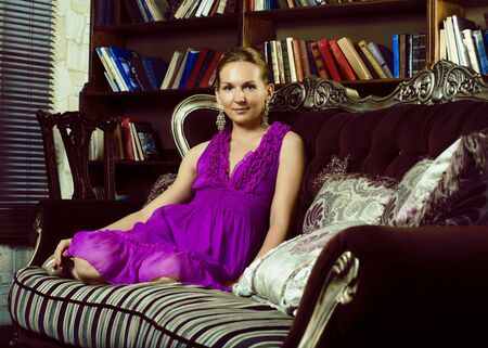 young pretty lady resting sexy on sofa with books, luxury style Imagens
