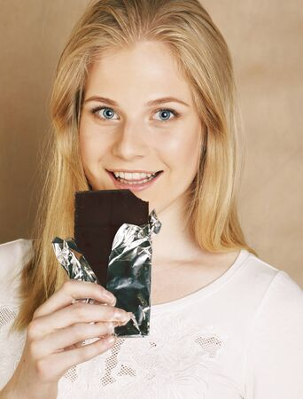 young cute blond girl eating chocolate and drinking coffee 写真素材