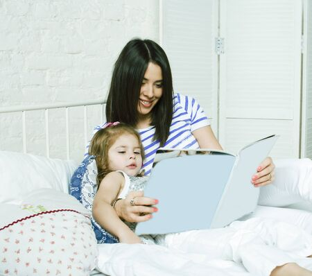 young mother with daughter at home playing, happy family