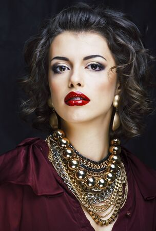 beauty rich brunette woman with a lot of gold jewellery, hispani