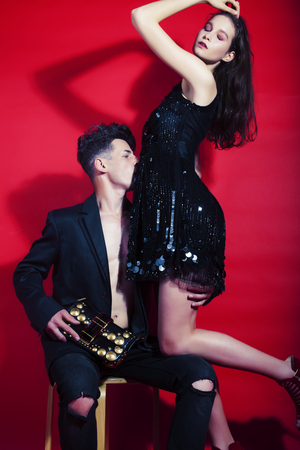 young fashion style couple man and woman on red background,