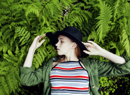 Pretty young blond girl hipster in hat among fern, vacation in g