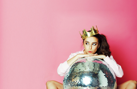 young cute party girl on pink background with disco ball and crown