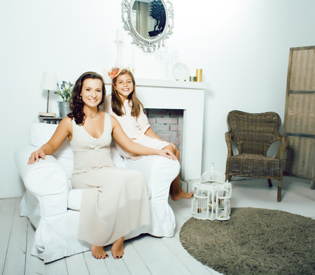 Portrait of smiling young mother and daughter at home, happy family together having fun, lifestyle people concept