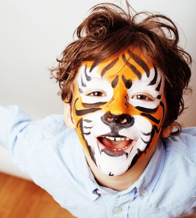 little cute boy with faceart on birthday party close up, little cute tiger Stock Photo