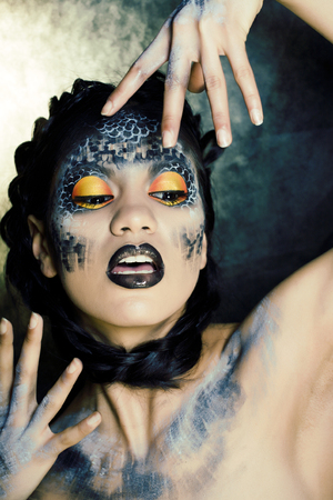 fashion portrait of pretty young woman with creative make up like a snake, halloween close up