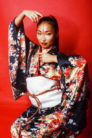 young pretty geisha on red background posing in kimono, oriental people lifestyle concept close up