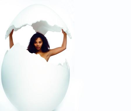 black skined woman in big crashed egg. modern easter hipster concept Foto de archivo