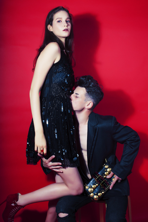 young fashion style couple man and woman on red background, luxury stuff, lifestyle modern people sale concept close up