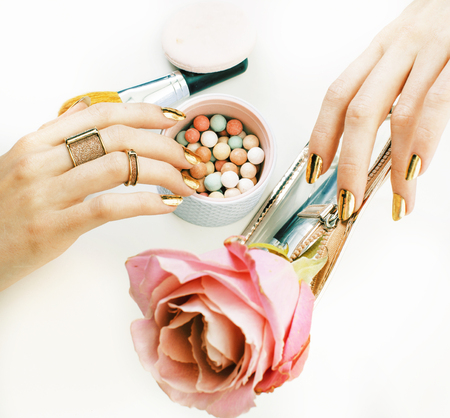 woman hands with golden manicure and many rings holding brushes, makeup artist stuff stylish, pure close up