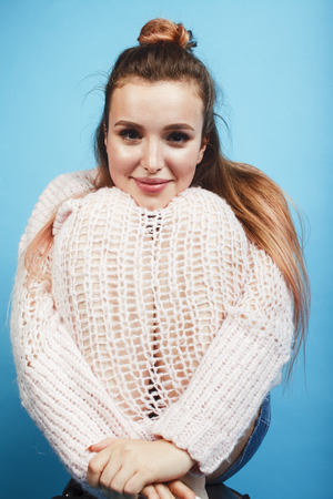 young pretty teenage modern hipster girl posing emotional happy on blue background, lifestyle people concept 스톡 콘텐츠