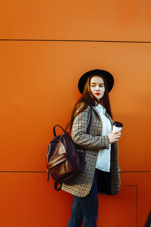 young pretty brunette business woman posing against modern building in hat holding coffee, lifestyle people concept