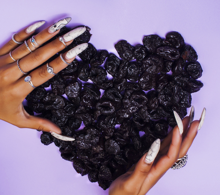 woman hands with long nails manicure holding fruits in shape of heart Фото со стока