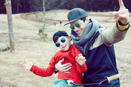 young father with his son having fun outside in spring field, happy family smiling, lifestyle people making selfie wearing sunglasses Stockfoto