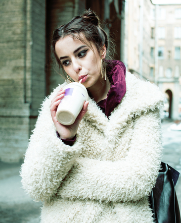 young pretty stylish teenage girl outside on city street fancy fashion dressed drinking milk shake, lifestyle concept