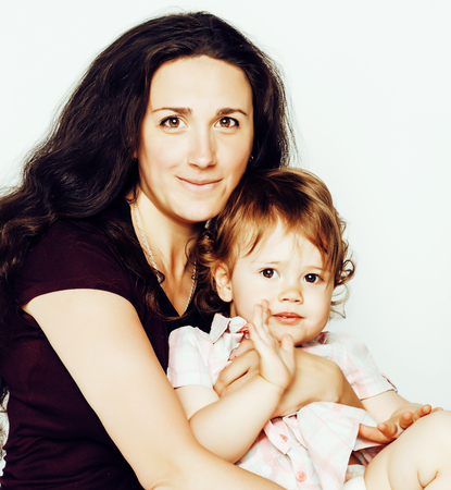 young modern smiling brunette mother with little cute daughter on white background, happy girls family inside isolated adorable