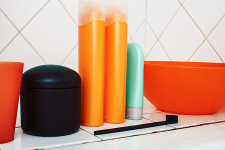 usual stuff in bathroom, shampoo, accessories, black stylish toothbrush, casual normal real background close up