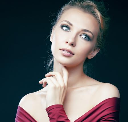 junge hübsche blonde Mädchen posiert sinnlich auf schwarzem Hintergrund im roten Body, Lifestyle-Leute-Konzept Standard-Bild