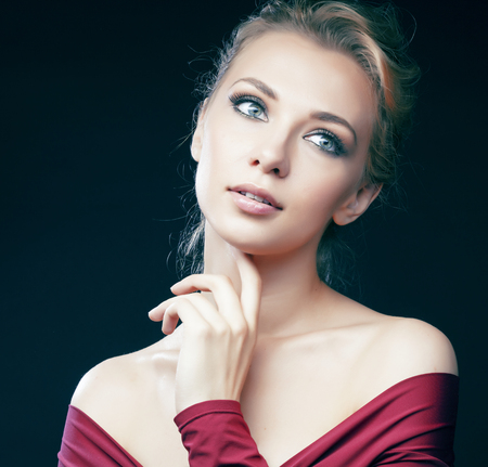 young pretty blond girl posing sensual on black background in red bodysuit, lifestyle people concept Stock fotó
