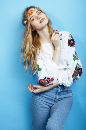 young pretty blond girl posing on blue background, fashion style hippie boho flowers on head closeup