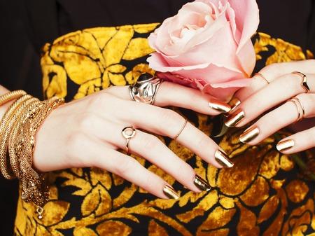 Frauenhände mit goldener Maniküre viel Schmuck auf ausgefallenem Kleid Nahaufnahme Schönheitskonzept