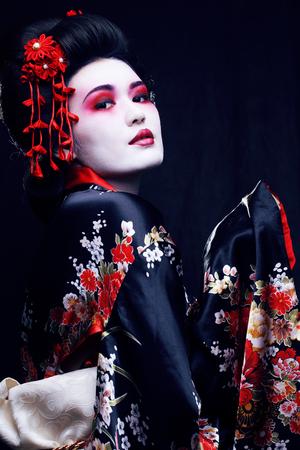 Joven geisha bastante real en kimono con sakura y decoración sobre fondo negro