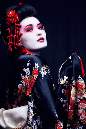 młoda ładna prawdziwa gejsza w kimonie z sakurą i dekoracją na czarnym tle