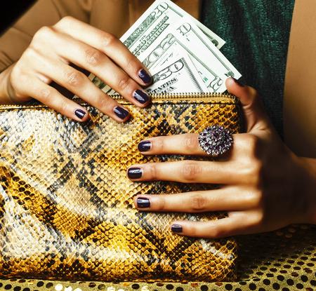 jolis doigts d'une femme afro-américaine tenant de l'argent en gros plan avec un sac à main, des bijoux de luxe sur une pochette en python, de l'argent pour des cadeaux