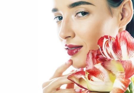 junge hübsche Brünette echte Frau mit roter Blume Amaryllis Nahaufnahme isoliert auf weißem Hintergrund. Ausgefallenes Mode-Make-up, heller Lippenstift, kreative, manikürte Ombre-Nägel