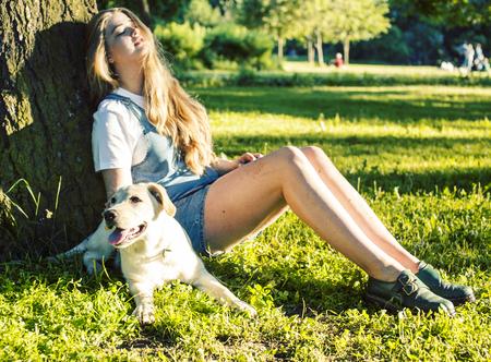 Joven y atractiva mujer rubia jugando con su perro en el parque verde en verano, concepto de pueblo de estilo de vida