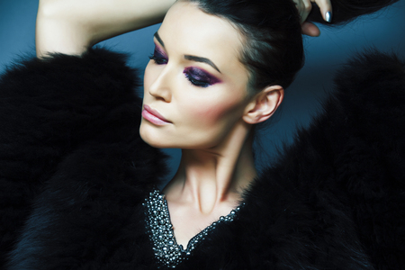 junges hübsches brünettes Mädchen mit Mode-Make-up, das elegant im Pelzmantel mit Schmuck auf blauem Hintergrund posiert, Lifestyle-Leute-Konzept Standard-Bild