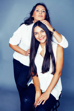 cute pretty teen daughter with mature mother hugging, fashion style brunette, lifestyle people concept close up