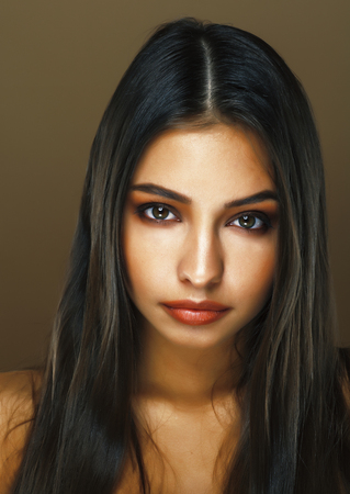 young pretty indian girl posing emotional on brown background, lifestyle people concept, fashion makeup Stock Photo