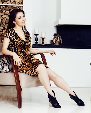 pretty stylish woman in fashion dress with leopard print in luxury house interior, lifestyle people concept Banco de Imagens