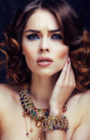 Mujer rica en belleza con maquillaje brillante vistiendo joyas de lujo parece madura de cerca, peinado rizado de dama de moda
