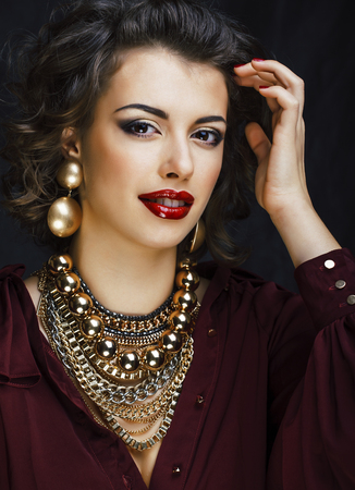 beauty rich brunette woman with a lot of gold jewellery, hispanic curly lady glamour on black background