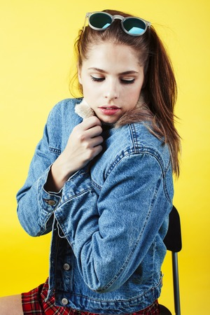 lifestyle people concept: pretty young school teenage girl having fun happy smiling on yellow background close up 스톡 콘텐츠