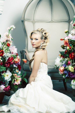 beauty young bride alone in luxury vintage interior with a lot of flowers, makeup and creative hairstyle Imagens