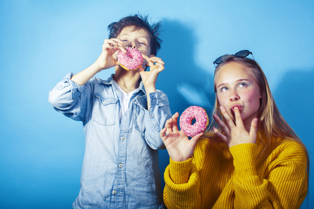 happy family brother and sister eating donuts on blue background, lifestyle people concept, boy and girl eating unhealthy Imagens