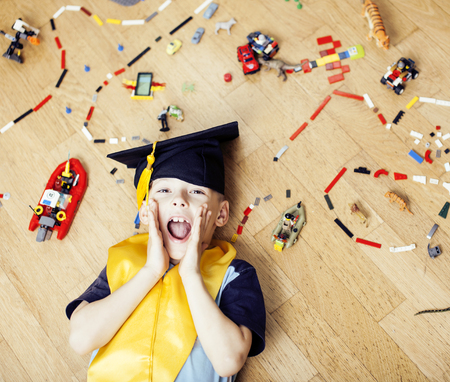 little cute preschooler boy playing toys at home happy smiling in graduation hat, lifestyle children , world map with pieces, self education concept Banque d'images - 123037130