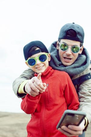 junger Vater mit seinem Sohn, der sich draußen im Frühlingsfeld amüsiert, glückliche Familie lächelt, Lifestyle-Leute, die Selfie mit Sonnenbrille machen
