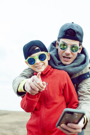 young father with his son having fun outside in spring field, happy family smiling, lifestyle people making selfie wearing sunglasses