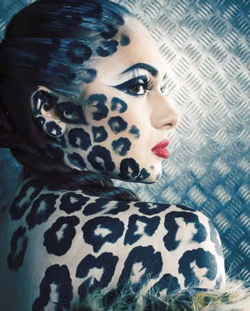 young woman with leopard make up all over body, cat bodyart print close up